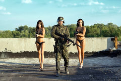 Soldier and two women. In underclothes with rifles royalty free stock photo