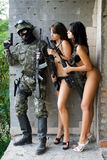 Soldier and two women. Armed soldier and two sexy women waiting in ambush Royalty Free Stock Images