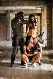 Soldier and two women. With rifles in the abandoned building royalty free stock photo