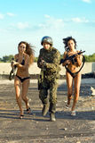 Soldier with two women. Soldier and two women with rifles running on the roof royalty free stock photo