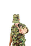 Soldier uniform and hat standing and showing the peace sign with Royalty Free Stock Images