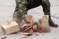 Soldier in uniform hits bricks. Male soldier in camouflage uniform hits bricks with bare hands Stock Image