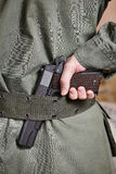 Soldier in uniform holding gun in his belt Royalty Free Stock Images