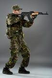 Soldier in uniform with machine gun. Studio portrait of an young soldier in uniform with machine gun, over gray background Royalty Free Stock Photo