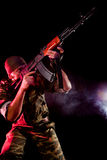 Soldier in uniform with rifle. Smoky background Royalty Free Stock Image