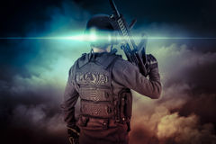 Soldier in uniform with rifle, assault sniper on apocalyptic clouds, firing. Power stock photography