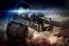 Soldier in uniform with rifle, assault sniper on apocalyptic clouds, firing. Power royalty free stock photo