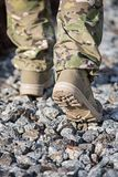 Soldier`s feet against the backdrop of stone soil Stock Image