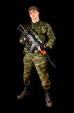 Soldier in uniform with weapon. Isolated on black background Stock Image
