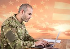 Soldier using a laptop in front of american flag Stock Photography