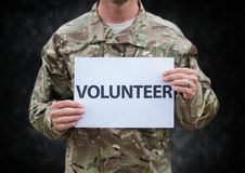 Soldier volunteer mid section against black grunge background stock photo