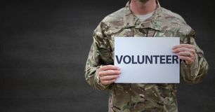 Soldier volunteer mid section against grey wall stock images