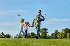 Soldier is walking with his family in the grass, back view. Patriotic family waving flags outdoors on the park meadow grass royalty free stock image