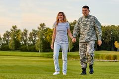 Soldier walking with wife holding hands. royalty free stock photos