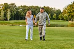 Soldier walking with woman, holding hands. royalty free stock image