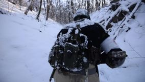 Soldier walks through a snowy forest stock video footage