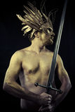 Soldier, Warrior with helmet and sword with his body painted gol Royalty Free Stock Images