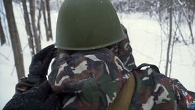 Soldier with weapons in cold forest. Winter warfare and military concept. Clip. Soldiers in winter forest on skis with stock photos