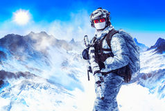 Soldier in winter uniforms. And white face mask in the mountains. Weapon wrapped with masking camouflage tape stock photography
