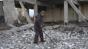 The soldier works with a mine detector in the ruins of houses in search of mines and explosives. Military operations in the world stock video footage