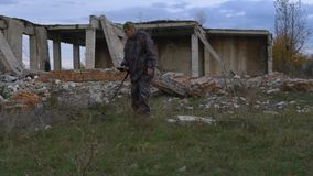 The soldier works with a mine detector in the ruins of houses in search of mines and explosives. Military operations in the world stock footage