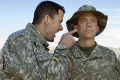 Soldier Yelling At Colleague. Military solider shouting at teammate during a training session Royalty Free Stock Photography
