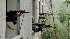 Soldiers aim target out of window stock video