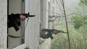 Soldiers aim target out of window stock video footage
