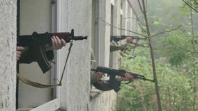 Soldiers aim target out of window stock footage