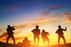 Soldiers in assault. War, army, military. Soldiers in assault shooting with weapon, rifle at sunset. War, army, military Stock Photo