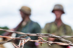 Soldiers and barbed wire. Focus on foreground barbed wire with soft focus soldiers in background Royalty Free Stock Image