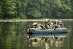 Soldiers in a boat sailing ahead. Operator in a boat sailing ahead royalty free stock photo
