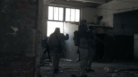 Soldiers in camouflage with combat weapons sneak along the corridors of the old building, the military concept. 4k Royalty Free Stock Image