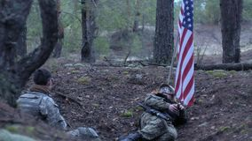 Soldiers in camouflage with combat weapons and in the US in the forest, military concept