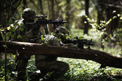 Soldiers in camouflage among trees Stock Image