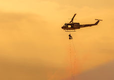Soldiers climb down from helicopter in military mission. Stock Image