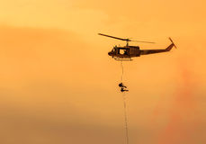 Soldiers climb down from helicopter in military mission. Royalty Free Stock Photo