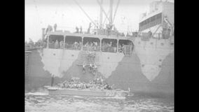 Soldiers climbing down rope ladder to landing crafts stock video