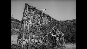 Soldiers climbing rope ladder in Army training camp, 1940s stock footage