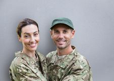 soldiers couple smiling. concrete wall royalty free stock photo