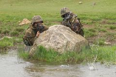 Soldiers covering behind the rock Royalty Free Stock Photography