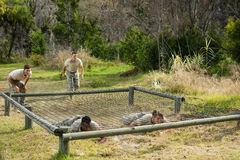 Soldiers crawling under the net during obstacle course Royalty Free Stock Photography