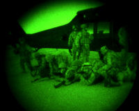 Soldiers Dismount Helicopter At Night. Soldiers rehearse getting unloaded from a helicopter before getting air lifted to the landing zone for their mission in Royalty Free Stock Photos