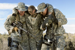 Soldiers In Field Carrying Colleague Stock Photos