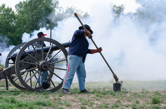 Soldiers firing a cannon. Union soldiers are shrouded on a smokey hilltop after firing off an old cannon Royalty Free Stock Photos