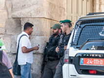 Soldiers guard the entrance to the old city of Jerusalem and talk with the local inhabitant in Jerusalem, Israel Royalty Free Stock Photo