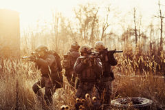 Soldiers with guns on the field Royalty Free Stock Photo