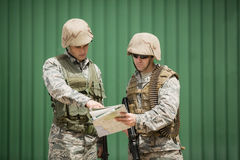 Soldiers having discussion over map. In boot camp stock photo