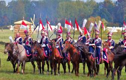 Soldiers in historical costumes hold flags and ride horses. Stock Photo