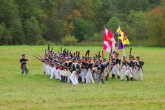 Soldiers in historical costumes march on the battle field with flags. Stock Photography